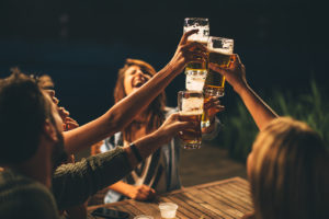 People laughing and cheering with beer